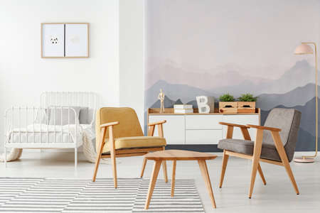Yellow and gray modern armchairs and a white bed in a multifunctional room interior with mountains wallpaper and wooden furniture Stock Photo