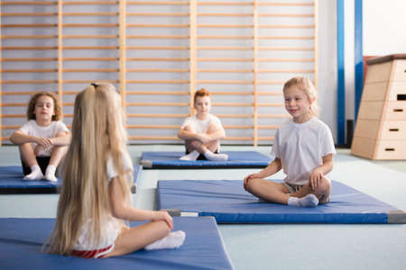 Happy young girls sitting across from each other on blue exercising mats with their legs crossed during PE classes in the primary school gym interior