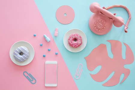 Pink and blue table top of a blogger with a phone, donuts, paper leaf and cd Stock Photo