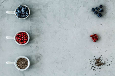 Top view of a symmetrical arrangement of blueberries, pomegranate and seeds on a gray table.
