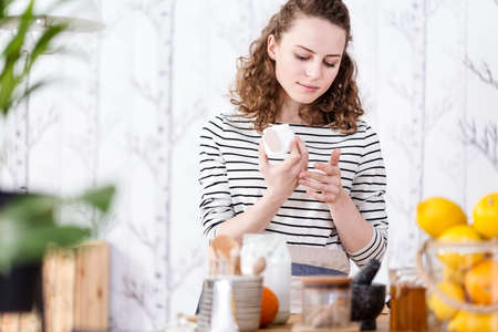 Woman testing vegan face cream made from organic, raw materials