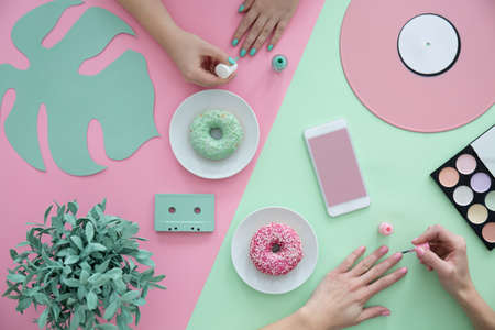 Girls painting nails on a pink and green table with donuts and plant