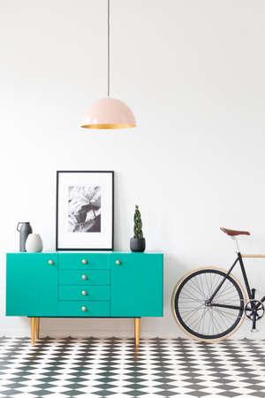 Pink lamp in vintage living room interior with bike next to green cabinet with plant and poster Stock Photo