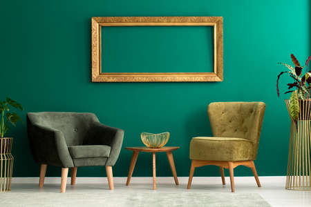 Gold frame hanging on the wall in green interior with two armchairs and decorative bowl on wooden table