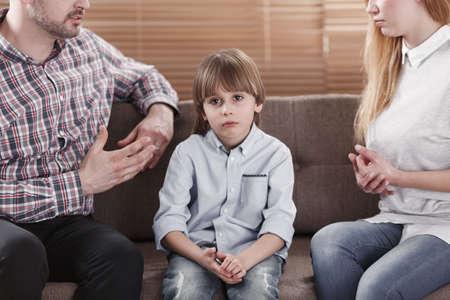 Primo piano del bambino triste e dei suoi genitori che discutono. Problema nel concetto di famiglia Archivio Fotografico