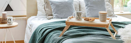 Close-up panorama of a wooden breakfast tray with cookies and coffee mugs on a cozy bed in bright bedroom interior Foto de archivo - 101899560