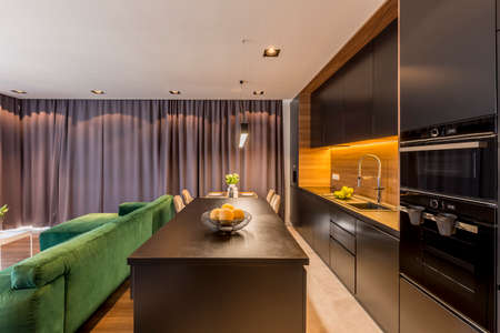 Kitchen island in dark open space interior with green couch and brown drapes