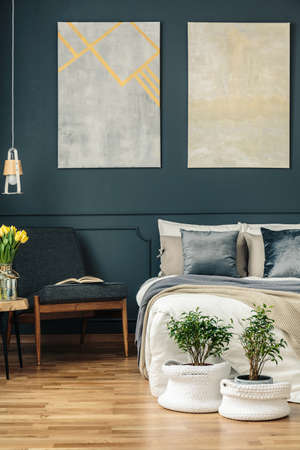 Vintage bedroom interior with armchair, bed, flowers, plants and paintings on the wall Stock Photo