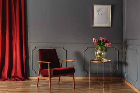 Red wooden armchair next to gold table with flowers in living room interior with poster