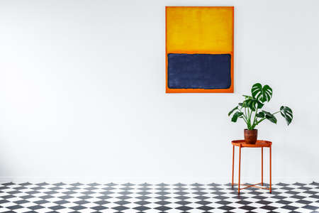 Orange table with plant on checkerboard floor in flat interior with painting on white wall with copy space Stock Photo
