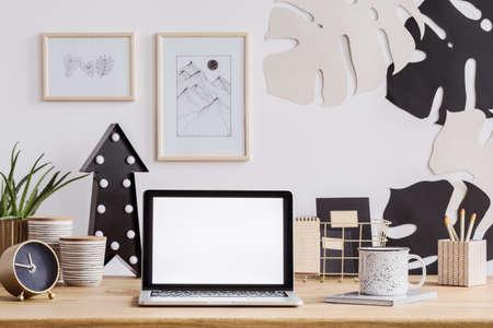 Laptop met wit scherm op een houten bureau met klok, mok en potloden en wanddecoraties