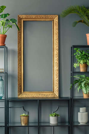 A gold frame and plants in vases on black shelves next to a grey wall