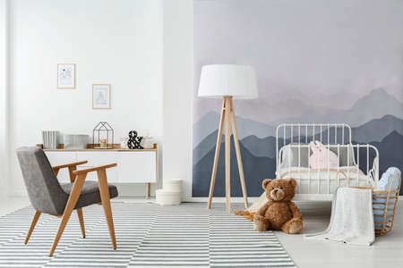 A wooden floor lamp and a modern gray armchair in a monochromatic childs bedroom interior in scandinavian style