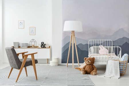 Una lampada da terra in legno e una moderna poltrona grigia in un interno monocromatico della camera da letto del bambino in stile scandinavo