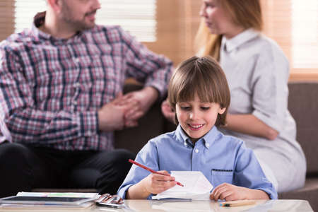 Close-up of smiling boy drawing a picture during therapy for autistic kids Stock Photo