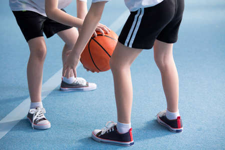 Close-up on young children wearing school sportswear learning to dribble a basketball during physical education classes in gym with blue floor