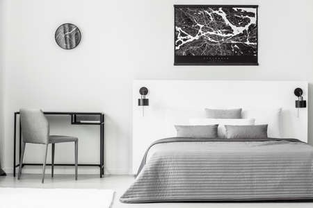 Black poster above grey and white bed in bedroom interior with chair at desk and clock 写真素材