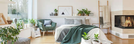 Natural bedroom interior with a cozy, white bed with decorative cushions standing between a fireplace and a green armchair. Real photo Stock Photo