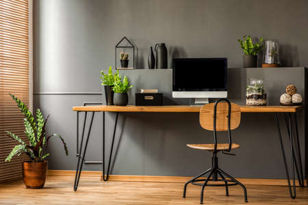 Simple workspace interior with wooden chair at the desk standing against black wall in a room with plants. Real photo Archivio Fotografico