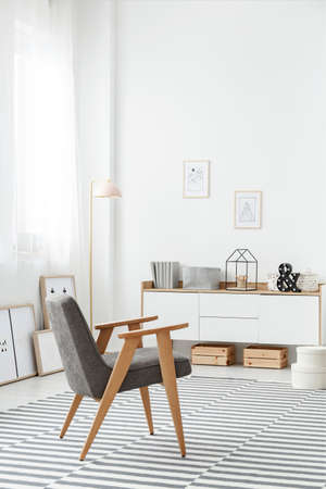 Wooden crates under a white sideboard and a comfortable, modern gray armchair in a stylish living room interior with a striped rug and white wall Stock Photo