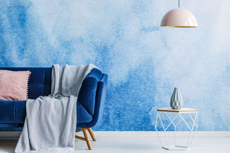 Blanket On Navy Blue Sofa In Living Room Interior With Pastel Pink Lamp  Above Table With