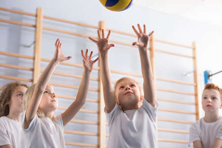 Young girl with her arms up jumping to hit a volleyball during a game with her school team mates at extracurricular physical education class in the gym