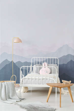 Wooden side table and a powder pink floor lamp by a childs metal frame bed in a sweet and cozy room interior Stock Photo