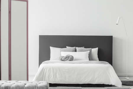 White lamp next to a bed with grey bedhead in minimal bedroom interior with pouf and screen 写真素材