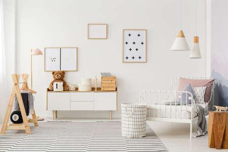Intérieur de chambre d'enfant naturel et lumineux avec des meubles en bois, des accessoires design et des affiches sur un mur blanc