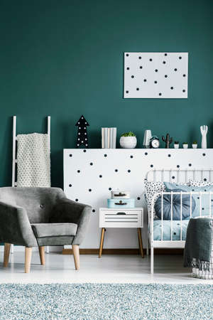 Grey suede armchair next to bed and cabinet in kids bedroom interior with poster on green wall Stock Photo