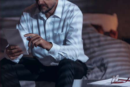 Low angle view of a mature male sitting on a bed in a room and holding a tablet in his hand with a woman sleeping under bed-cover in a blurred background