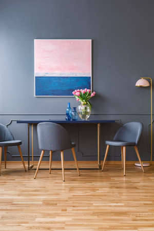 Wooden chairs at table with pink flowers in elegant dining room interior with painting and lamp