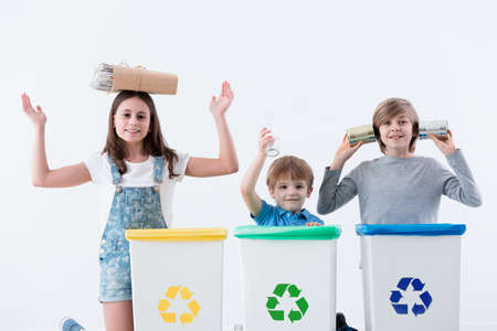 Happy children having fun while segregating household waste into bins with recycling symbol against white background Foto de archivo