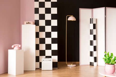 Pink phone on white pedestal in studio interior with lamp next to a screen and checkerboard wall 스톡 콘텐츠