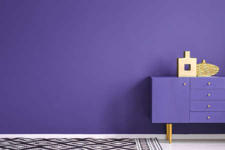 Gold vases on violet cabinet in anteroom interior with patterned carpet and copy space on purple wall