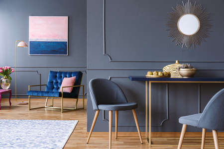 Chair at table in modern grey apartment interior with navy blue armchair, painting and mirror