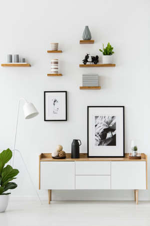 Plakat na drewnianej szafce w białym wnętrzu salonu z lampą i rośliną. Prawdziwe zdjęcie