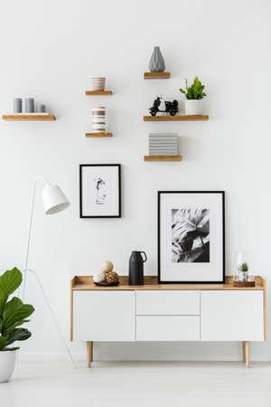Poster op houten kast in wit woonkamer interieur met lamp en plant. Echte foto