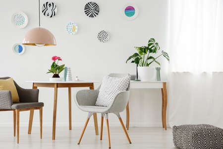 Retro armchairs, table, chandelier, ceramic wall decoration and pouf in a bright apartment interior