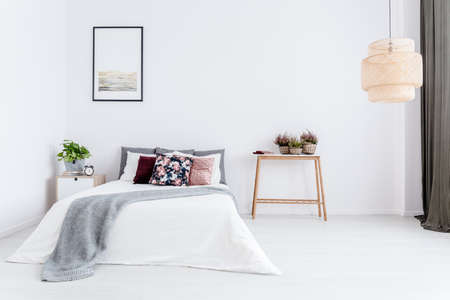 Simple, white bedroom interior with floral pillow and gray blanket on the bed Фото со стока