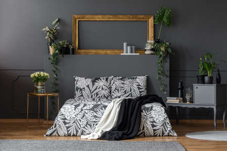 Luxurious, dark apartment room interior with a cozy double bed, elegant gray furniture, gold decorations and plants
