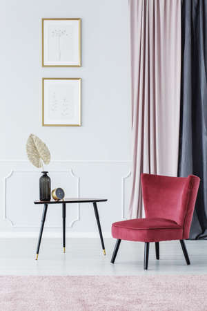 Burgundy chair standing by a black table with decorative leaf and clock in bright room interior with posters