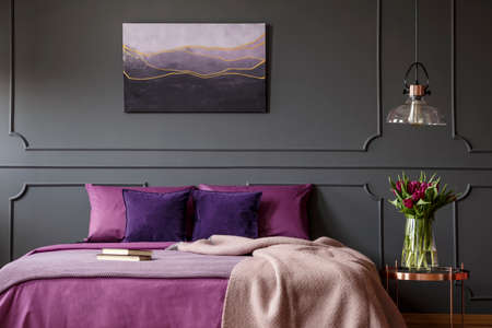 Blanket on purple bed next to table with flowers in bedroom interior with poster on grey wall Foto de archivo