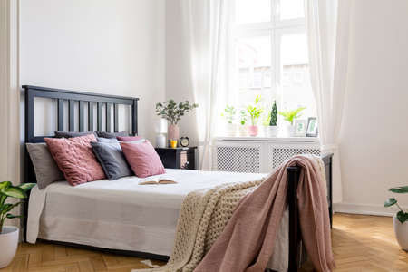 Pink blanket on bed with black headboard in bright bedroom interior with plants and window. Real photo Archivio Fotografico - 101667515