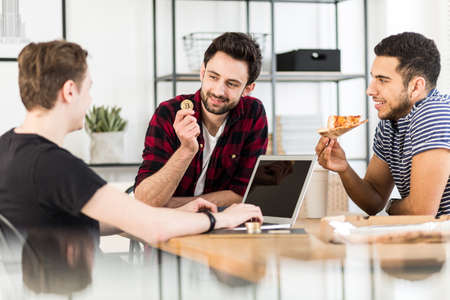 Man eating pizza and his friend holding a gold coin. Cryptocurrency concept