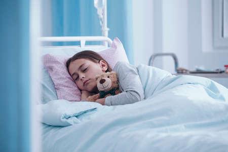 Sick girl sleeping with teddy bear in the hospital Stockfoto