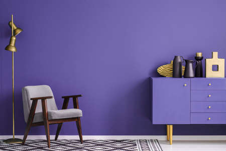 Black vases on violet cabinet near grey armchair and lamp in living room interior with patterned carpet Stock fotó