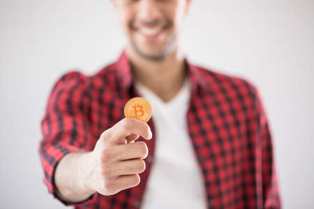 Close-up of man holding gold BitCoin - digital cryptocurrency