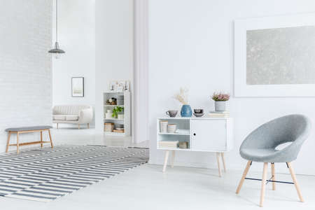 Ampio soggiorno interno con pittura d'argento appesa sopra una poltrona grigia e armadio in legno con decorazioni