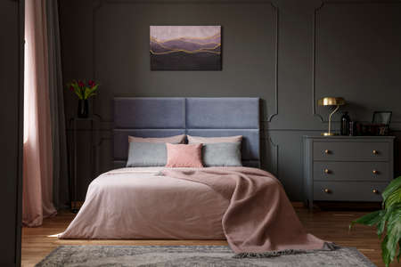 Gold lamp on grey cabinet next to bed in pastel bedroom interior with violet painting